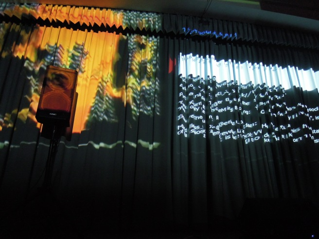 #MAX's visuals included a changing screenshot of text. The curtain distorted it into a babble of language, matching the performance's tangle of speech and sound.